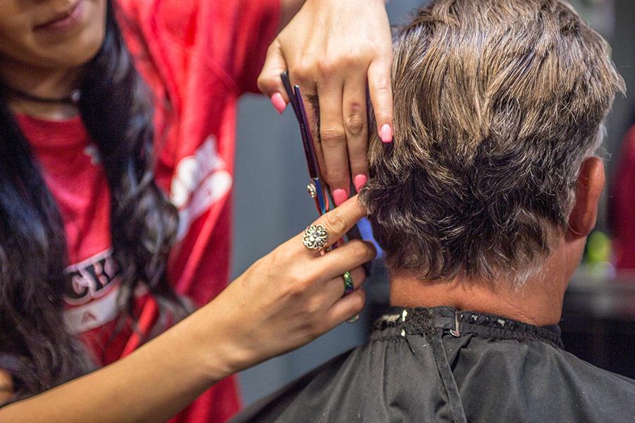 Locker Room Haircuts stylist cutting a man's hair.
